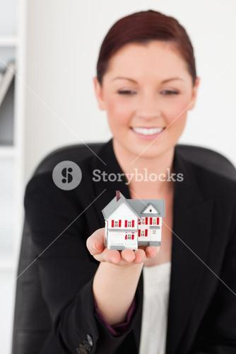 Beautiful redhaired woman in suit holding a miniature house