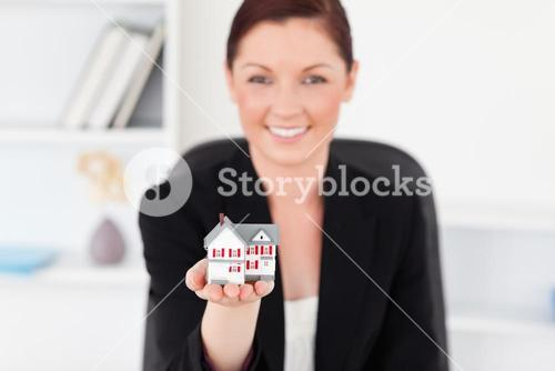 Pretty redhaired woman in suit holding a miniature house