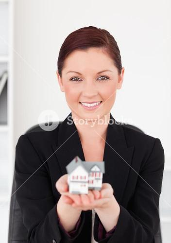 Cute redhaired woman in suit holding a miniature house