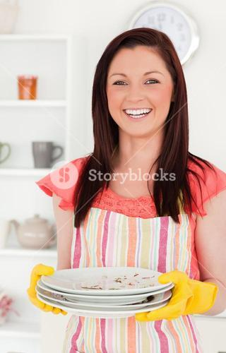 Beautiful redhaired woman holding some dirty plates in the kitchen