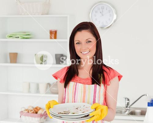 Attractive redhaired woman holding some dirty plates in the kitchen