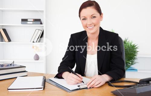 Beautiful redhaired female in suit writing on a notepad and posing