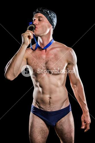 Swimmer kissing his gold medal