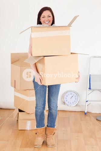 Good looking redhaired woman holding some carboard boxes