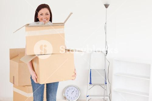 Attractive redhaired woman holding some carboard boxes