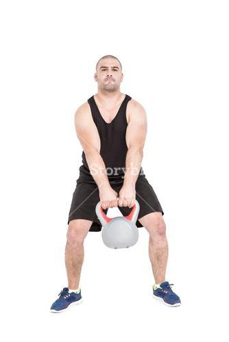 Bodybuilder lifting heavy kettlebell