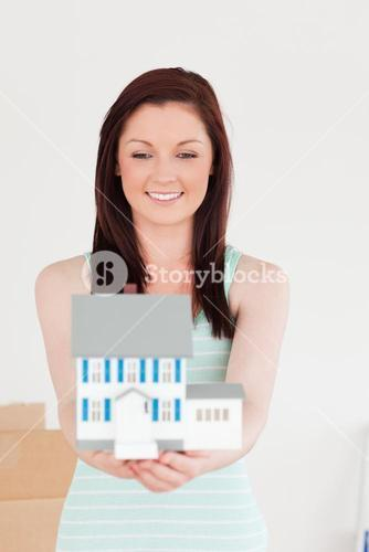 Good looking redhaired woman holding a miniature house while standing on the floor