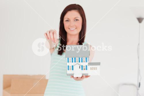 Good looking redhaired female holding a miniature house while standing on the floor