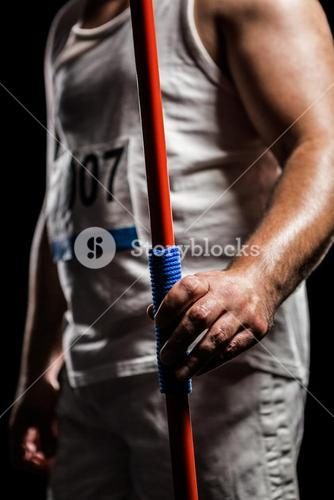 Mid section of athlete standing with javelin