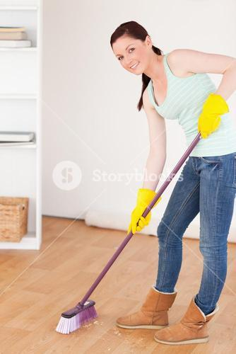 Good lookingl redhaired woman sweeping the floor at home