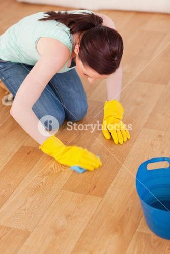 Good looking redhaired woman cleaning the floor while kneeling