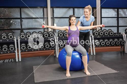 Trainer helping pregnant woman at the gym