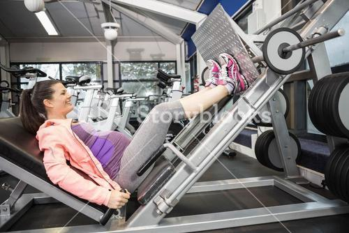 Pregnant woman using weight machine
