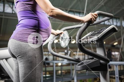 Pregnant woman standing on a fitness machine