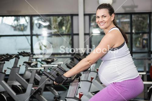 Pregnant woman using exercise bike