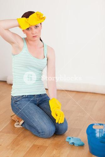 Good looking redhaired woman having a break while cleaning the floor