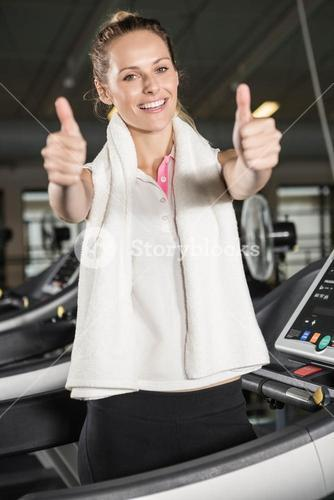 Smiling woman in sportswear showing thumbs up