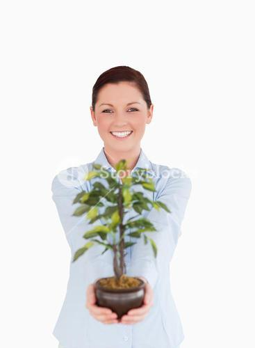Good looking redhaired female holding a houseplant while standing