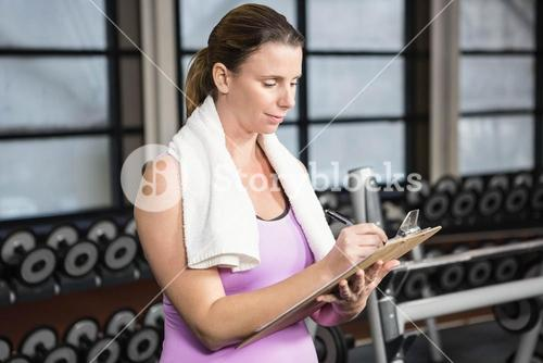 Pregnant woman writing on clipboard