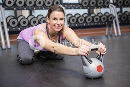 Smiling woman exercising with kettlebell