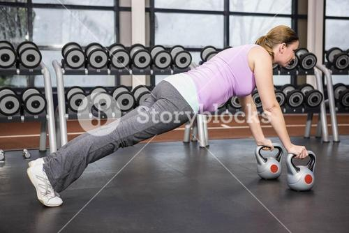 Determined woman planking with kettlebells
