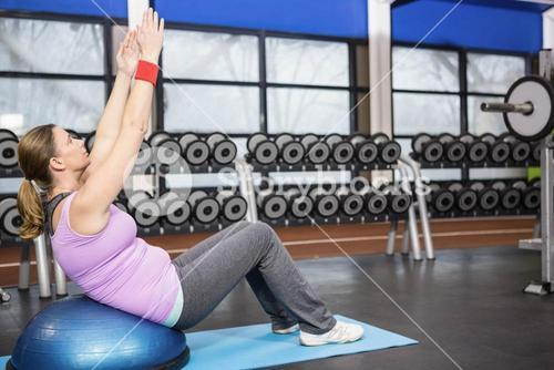 Determined woman exercising with bosu ball