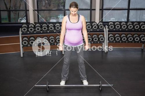 Determined woman looking at barbell