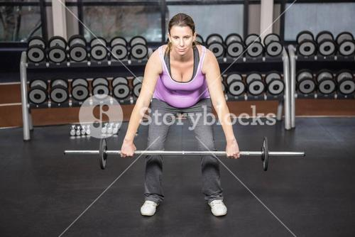 Determined woman lifting barbell