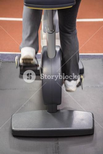 Lower section of woman on exercise bike