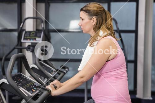 Pregnant woman on exercising bike