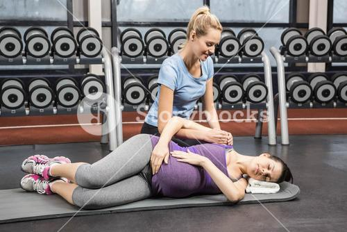 Smiling trainer manipulating pregnant woman