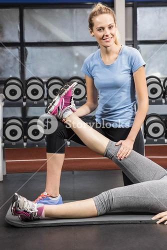 Smiling trainer stretching pregnant womans leg