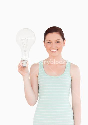 Gorgeous redhaired female holding a bulb while standing