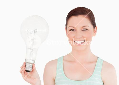 Attractive redhaired female holding a bulb while standing