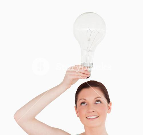 Gorgeous redhaired woman holding a bulb while standing