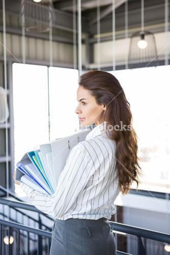 Busy businesswoman carrying folders with files documents