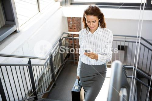 Businesswoman using phone and climbing staircase