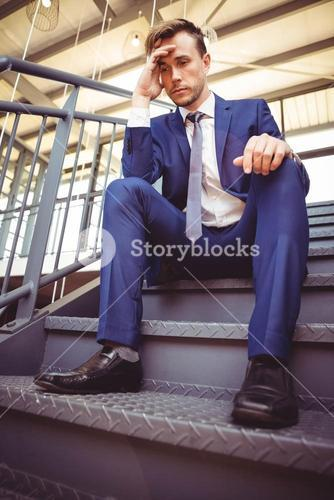 Worried businessman sitting on stairs