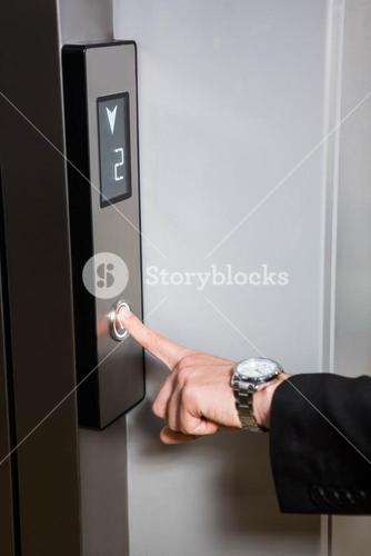 Businessman pressing elevator button