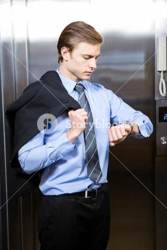 Businessman checking time while waiting for elevator