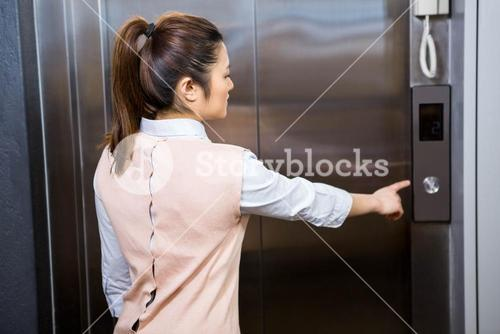 Businesswoman pressing elevator button