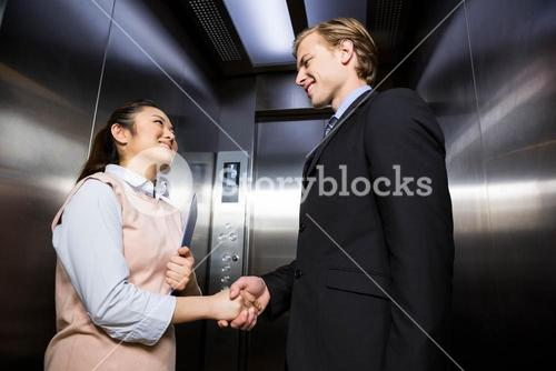 Businessman shaking hands with businesswoman in elevator