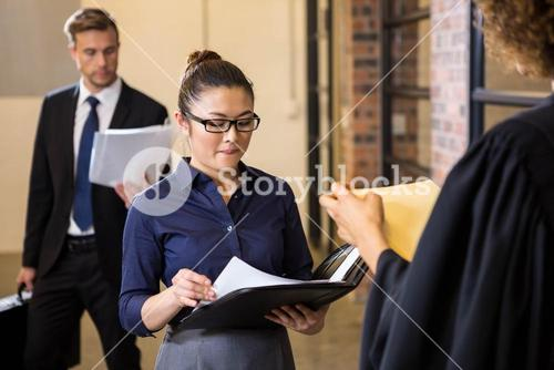 Lawyer looking at documents and interacting with businesswoman