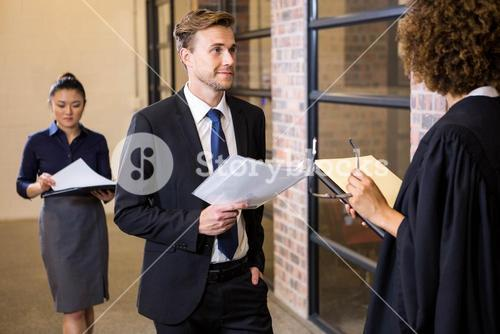 Lawyer looking at documents and interacting with businessman