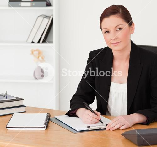 Good looking redhaired woman in suit writing on a notepad