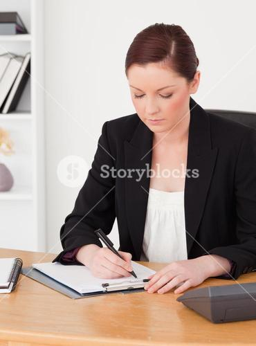 Beautiful redhaired woman in suit writing on a notepad