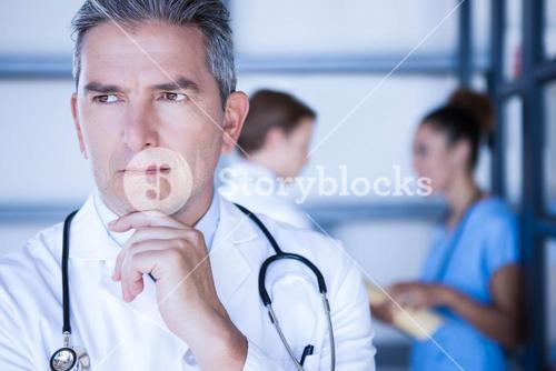Thoughtful doctor standing in hospital
