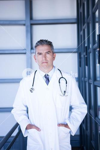 Serious male doctor standing with hands in pocket