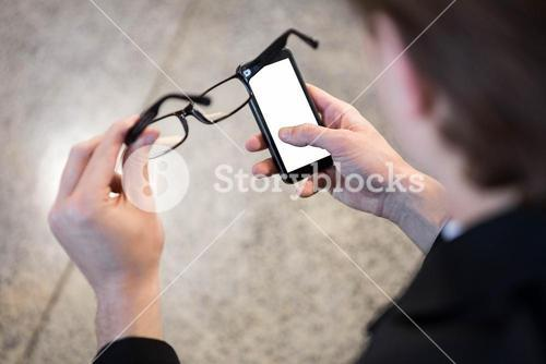 Businessman text messaging on mobile phone