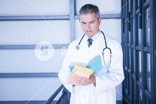 Male doctor reading medical book